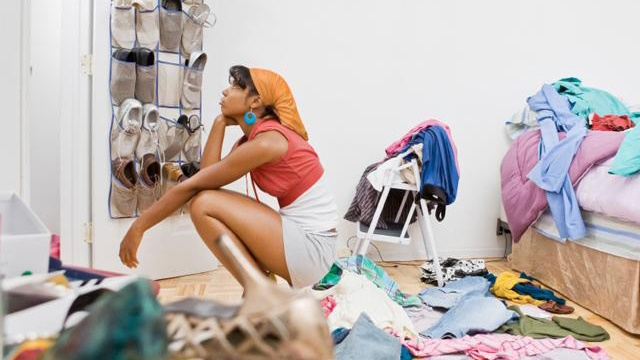 a young woman staring at all her clothes (Photo Credit: http://www.sheknows.com/)
